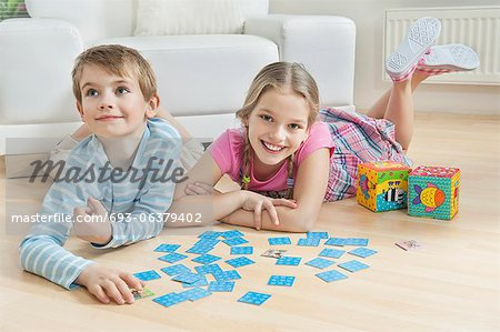 Portrait of a girl and little brother lying on floor with cards Stock Photo - Premium Royalty-Free, Image code: 693-06379402