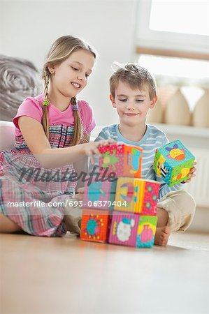 Children stacking blocks while sitting on floor Stock Photo - Premium Royalty-Free, Image code: 693-06379404