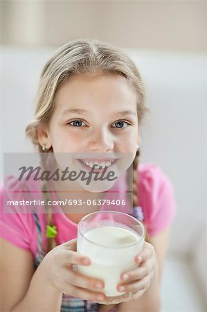 Portrait of happy young girl drinking milk Stock Photo - Premium Royalty-Free, Image code: 693-06379406