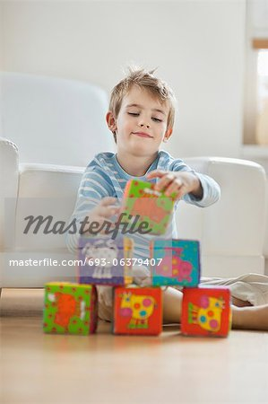 Little boy stacking blocks while sitting on floor Stock Photo - Premium Royalty-Free, Image code: 693-06379407