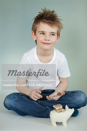 Thoughtful boy with piggy bank and coins over gray background Stock Photo - Premium Royalty-Free, Image code: 693-06379421