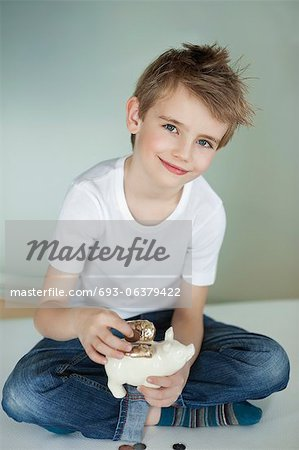 Portrait of young boy putting coin in piggy bank Stock Photo - Premium Royalty-Free, Image code: 693-06379422