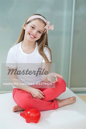 Portrait of girl with piggy bank and coins sitting in bed Stock Photo - Premium Royalty-Free, Image code: 693-06379426