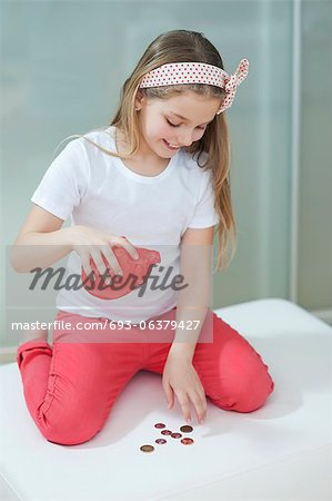 Young girl with piggy bank counting coins on bed Stock Photo - Premium Royalty-Free, Image code: 693-06379427