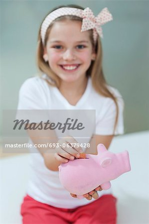 Portrait of a happy girl putting coin in piggy bank Stock Photo - Premium Royalty-Free, Image code: 693-06379428