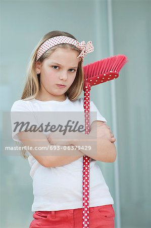 Portrait of an angry girl with broom Stock Photo - Premium Royalty-Free, Image code: 693-06379429