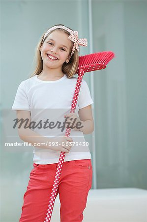 Portrait of a happy young girl with broom Stock Photo - Premium Royalty-Free, Image code: 693-06379430