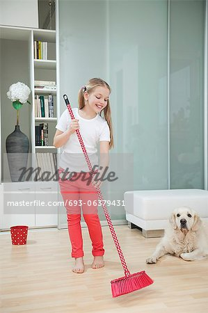 Girl sweeping the floor Stock Photo - Premium Royalty-Free, Image code: 693-06379431