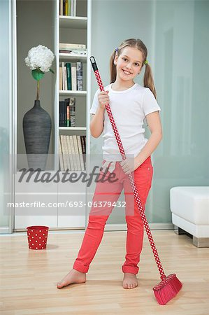 Portrait of a young girl sweeping floor with broom Stock Photo - Premium Royalty-Free, Image code: 693-06379432