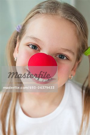 Close-up portrait of a happy girl with red clown nose Stock Photo - Premium Royalty-Free, Image code: 693-06379433