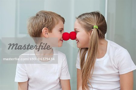 Happy young siblings in white tshirts rubbing clown noses against each other Stock Photo - Premium Royalty-Free, Image code: 693-06379434