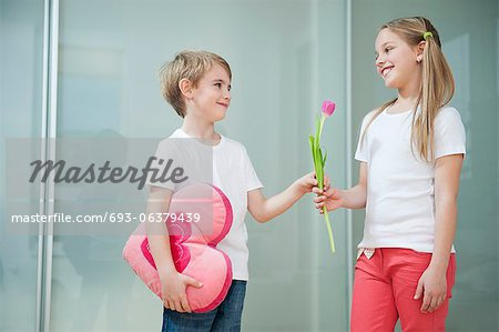 Little boy with heart shape cushion giving flower to girl Stock Photo - Premium Royalty-Free, Image code: 693-06379439