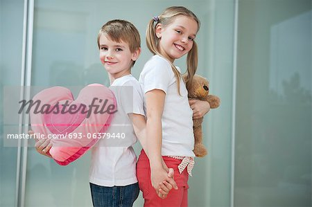 Boy and girl with heart shape cushion and teddy bear holding hands while standing back to back Stock Photo - Premium Royalty-Free, Image code: 693-06379440