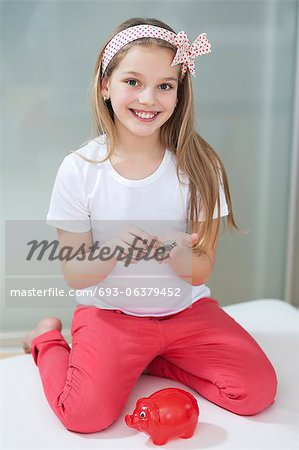 Portrait of girl with piggy bank and coins sitting in bed Stock Photo - Premium Royalty-Free, Image code: 693-06379452