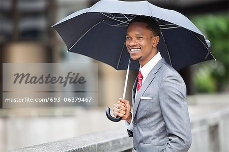 Happy African American businessman holding umbrella Stock Photo - Premium Royalty-Free, Image code: 693-06379467
