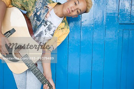 Portrait of a teenage boy playing guitar against wood paneled wall Stock Photo - Premium Royalty-Free, Image code: 693-06379489
