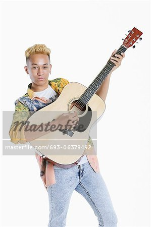 Portrait of a teenage boy playing guitar over gray background