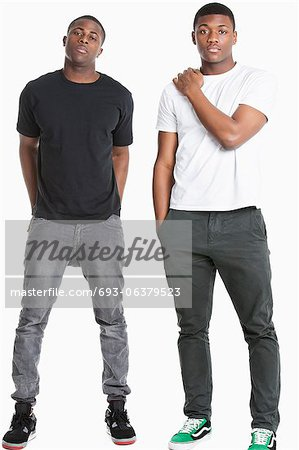 Portrait of two young men in casuals over gray background Stock Photo - Premium Royalty-Free, Image code: 693-06379523