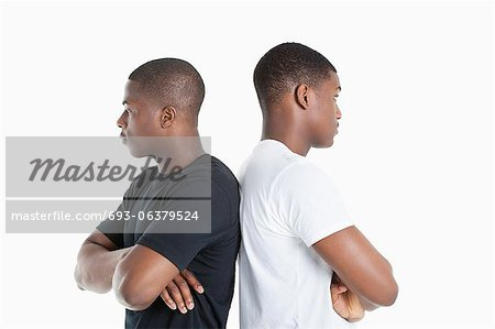 Two male friends standing back to back over gray background Stock Photo - Premium Royalty-Free, Image code: 693-06379524