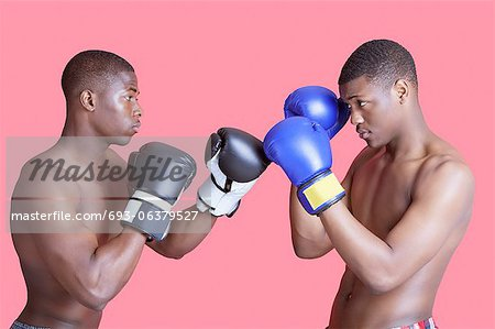 Side view of two African American boxers in fighting stance over pink background Stock Photo - Premium Royalty-Free, Image code: 693-06379527