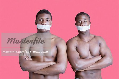 Portrait of two muscular African American men with tapes covering mouth over pink background Stock Photo - Premium Royalty-Free, Image code: 693-06379530