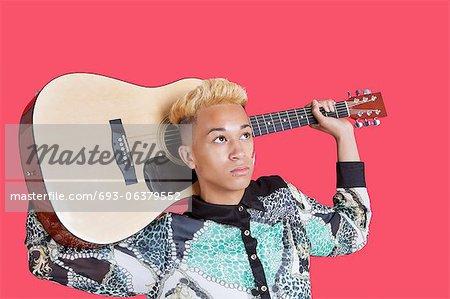 Teenage boy carrying guitar over his shoulder over pink background