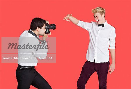 Male actor being photographed by paparazzi over red background Stock Photo - Premium Royalty-Free, Image code: 693-06379561