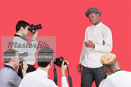 Paparazzi taking photographs of male actor over red background Stock Photo - Premium Royalty-Free, Image code: 693-06379565