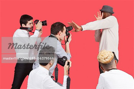 Young male celebrity shielding face from photographers over red background Stock Photo - Premium Royalty-Free, Image code: 693-06379566