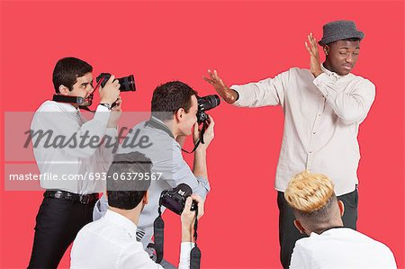 Young male celebrity shielding face from photographers over red background Stock Photo - Premium Royalty-Free, Image code: 693-06379567