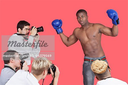 Paparazzi taking photographs of male boxer over red background Stock Photo - Premium Royalty-Free, Image code: 693-06379569