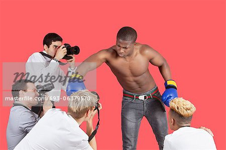 Paparazzi taking photographs of male boxer over red background Stock Photo - Premium Royalty-Free, Image code: 693-06379570