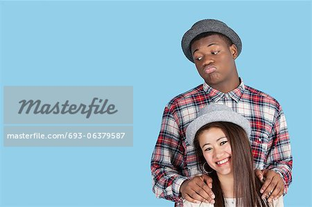 Bored African American man with smiling girlfriend over blue background Stock Photo - Premium Royalty-Free, Image code: 693-06379587