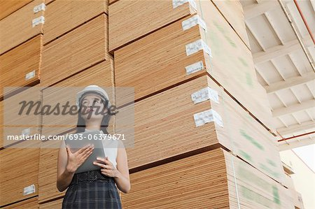 Low angle view of female industrial worker holding tablet PC with stacked wooden planks in background Stock Photo - Premium Royalty-Free, Image code: 693-06379671
