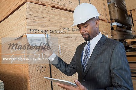 African American male contractor using tablet PC while inspecting wooden planks Stock Photo - Premium Royalty-Free, Image code: 693-06379710
