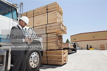 African American male contractor using tablet PC while standing by logging truck Stock Photo - Premium Royalty-Free, Image code: 693-06379723