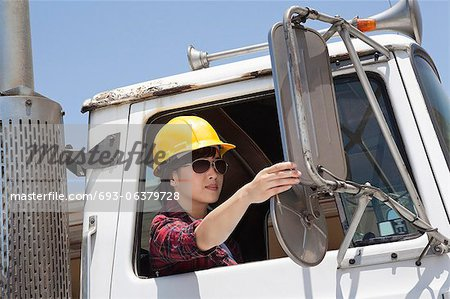 Asian female industrial worker adjusting mirror while sitting in logging truck Stock Photo - Premium Royalty-Free, Image code: 693-06379728