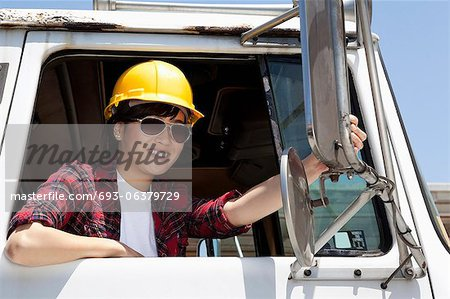 Female industrial worker adjusting mirror while sitting in logging truck Stock Photo - Premium Royalty-Free, Image code: 693-06379729