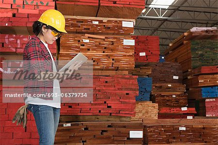 Side view of an Asian female industrial worker working on tablet PC with stacked wooden planks in background Stock Photo - Premium Royalty-Free, Image code: 693-06379734