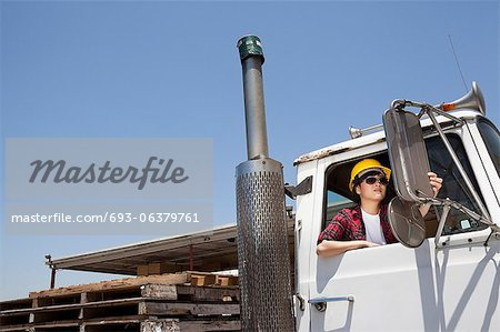 Female industrial worker adjusting mirror while sitting in logging truck Stock Photo - Premium Royalty-Free, Image code: 693-06379761