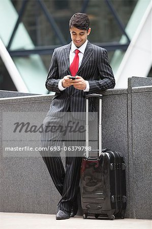 Young Indian businessman with luggage bag using cell phone Stock Photo - Premium Royalty-Free, Image code: 693-06379798