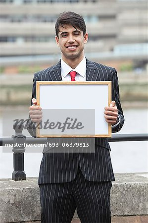 Portrait of young Indian businessman holding blank sign Stock Photo - Premium Royalty-Free, Image code: 693-06379813