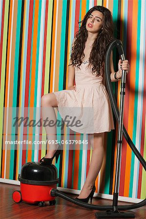 Portrait of young woman with vacuum cleaner standing against colorful striped wall Stock Photo - Premium Royalty-Free, Image code: 693-06379845