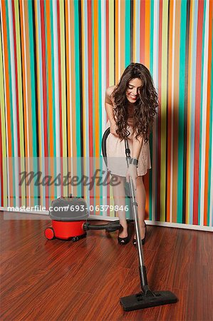 Happy young woman cleaning hardwood floor using vacuum cleaner Stock Photo - Premium Royalty-Free, Image code: 693-06379846