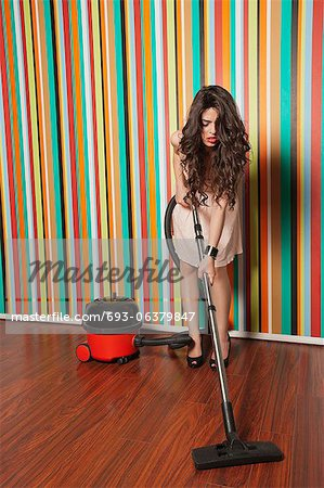 Young woman cleaning hardwood floor with vacuum cleaner Stock Photo - Premium Royalty-Free, Image code: 693-06379847