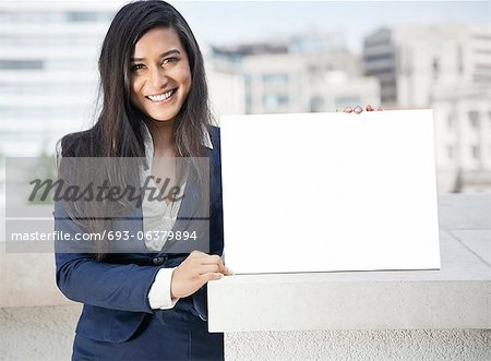 Portrait of a young Indian businesswoman holding Moodboard sign Stock Photo - Premium Royalty-Free, Image code: 693-06379894