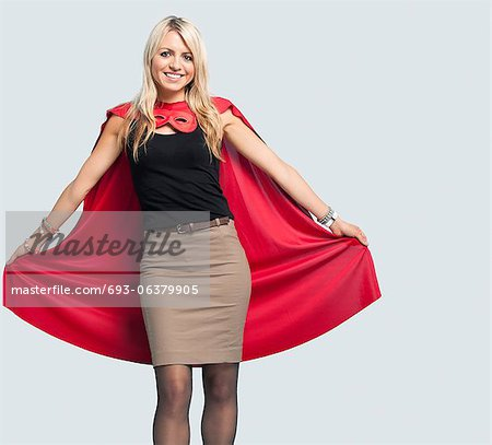 Portrait of beautiful woman in superhero costume over light blue background Stock Photo - Premium Royalty-Free, Image code: 693-06379905
