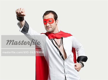 Young man wearing superhero costume against gray background Stock Photo - Premium Royalty-Free, Image code: 693-06379908