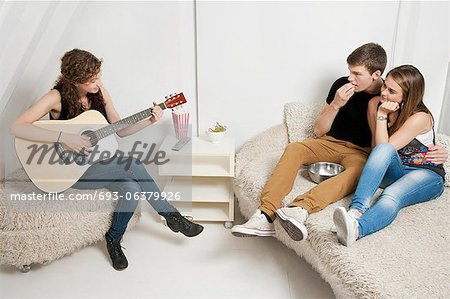 Young woman playing guitar with friends sitting on sofa Stock Photo - Premium Royalty-Free, Image code: 693-06379926