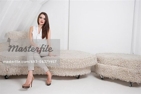 Portrait of beautiful young woman sitting on sofa Stock Photo - Premium Royalty-Free, Image code: 693-06379957